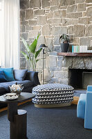 Side table, pouf and sofa in front of natural stone wall in living room