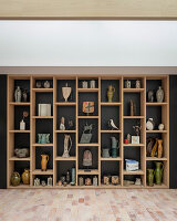 Vasen, Krüge und Skulpturen in modernem Regal vor dunkler Wand