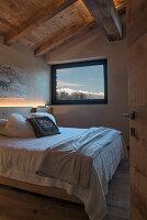 Doppelbett und Panoramafenster im Schlafzimmer mit Holzbalkendecke