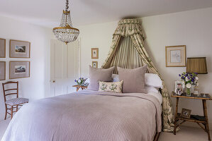 Romantic bedroom with chandelier and canopy add a touch of glamour