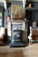 Old stove in front of fireplace with religious painting on mantelpiece and vintage-style accessories