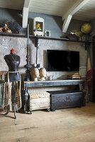 Schneiderpuppe neben altem Konsolentisch mit Truhen und Fernseher