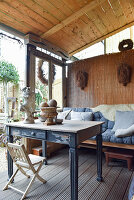 Old table and bench on roofed terrace with vintage-style accessories