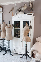 Old tailors' dummies in front of white glass-fronted cabinet with stuffed birds on top