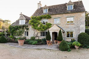 Climbing plant and porch entrance on facade of Cotswold stone farmhouse