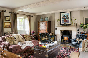 Buttoned chairs at lit fireside with animal skin on sofa and black travelling chest