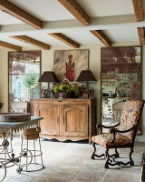 Antique chair with distressed mirrors and wooden sideboard with lamps.