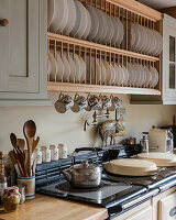 Wooden plate rack above stove with kettle on hob
