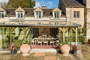 View into dining room of glass conservatory extension to 19th century stone farmhouse.