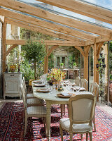 Dining room in glass conservatory extension of 19th century stone farmhouse.