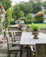Table and chairs on terrace with climbing rose