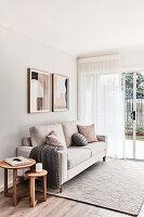 Sofa vor der Terrassentür im hellen Wohnzimmer in Beige