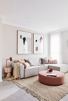 Round ottoman in modern living room decorated in pale grey and ecru