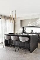 Gepolsterte Barhocker an der Kücheninsel in moderner Küche in Grau