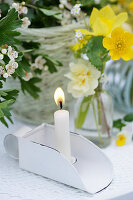 Lit candle next to posy of primroses, buttercups and tulips