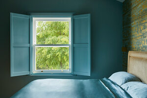 Double bed and open window shutters in bedroom with blue wall