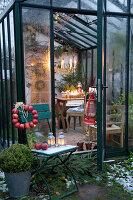 Stuhl mit Apfelkranz vor weihnachtlich dekoriertem Wintergarten