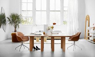 Doppeltische mit eleganten Schalenstühlen in weißer, luftiger Ambiente