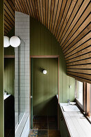 Schmales Badezimmer mit grüner Holzverkleidung und gebogener Holzdecke