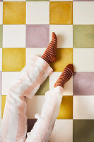 Damenbeine auf Fliesenboden