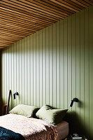 Doppelbett im Schlafzimmer mit grün gestrichener Holzverkleidung