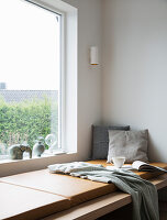 Large cushions on wide window seat used as daybed