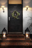 Christmas wreath on front door flanked by wall-mounted lamps and candle lanterns on steps