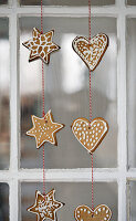 Gingerbread shapes threaded on string hung in window