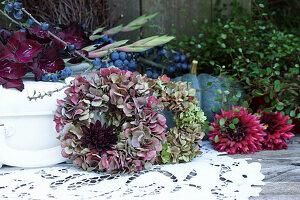 Herbst Arrangement mit Kränzen aus Hortensienblüten, Dahlienblüten, Speisekürbis, Schlehenzweig und Gladiole