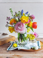 Spring bouquet of ranunculus, tulips, narcissus, grape hyacinths and waxflowers