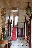 Theatrical entrance hall with with rubbed silver foil wallpaper, gilt framed mirror and burgundy felt palanquin