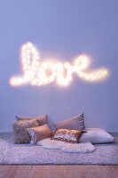Fairy lights spelling 'LOVE' and various cushions on the floor