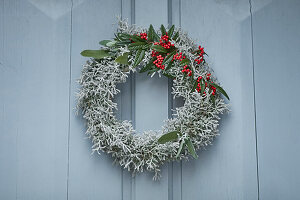 Wreath of santolina and cotoneaster with red berries on door