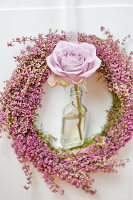 Heather wreath with rose in small bottle decorating door