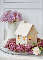House-shaped tealight lantern in wreath of heather and vase of purple roses