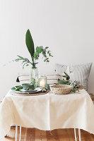 Sommerlich gedeckter Tisch mit mediterranem Blattgrün