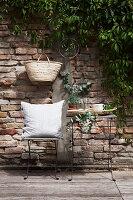 Sitzplatz mit mediterranem Blattgrün vor Backsteinmauer