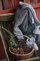 Basket of fir cones and branches, cardigan and scarf