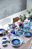 A table laid for Christmas dinner with blue-and-white crockery and pink flowers