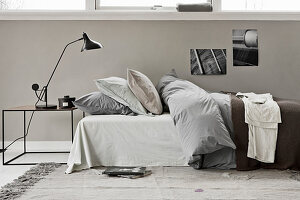 A bed with a duvet and pillows and a bedside table with a reading lamp