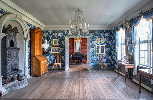 A minimalist room with console tables, a cast iron stove, a bureau and blue patterned wallpaper