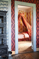 A view into a bedroom with a four-poster bed and wallpaper