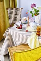 Gedeckter Kaffeetisch mit Erdbeeren, Blume und gestreifter Tischdecke