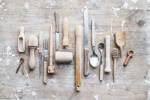 Verschiedene Küchenwerkzeuge mit Holzgriff auf Holzbrett