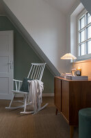A rocking chair and a chest of drawers in front of an attic window