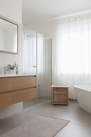 A washbasin, a shower area with a glass door and a freestanding bathtub in a bathroom