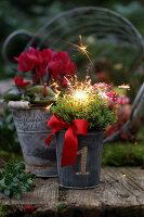 Neujahrsgesteck mit Wunderkerze im Freien