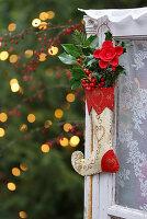 Nikolausstiefel mit roten Beeren und Blättern am Fenster
