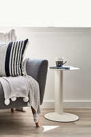 Scatter cushions and blanket on sofa next to side table