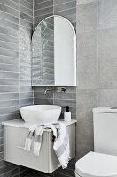Washstand with countertop sink below mirror